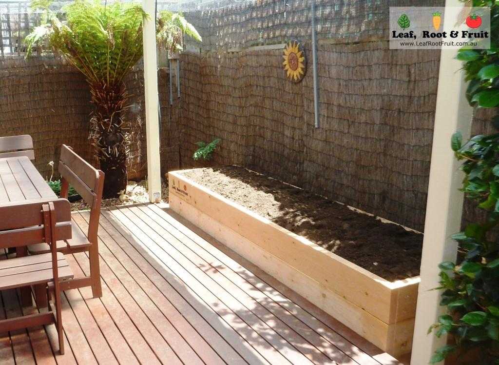 A long narrow cypress sleeper vegetable raised garden along a patio