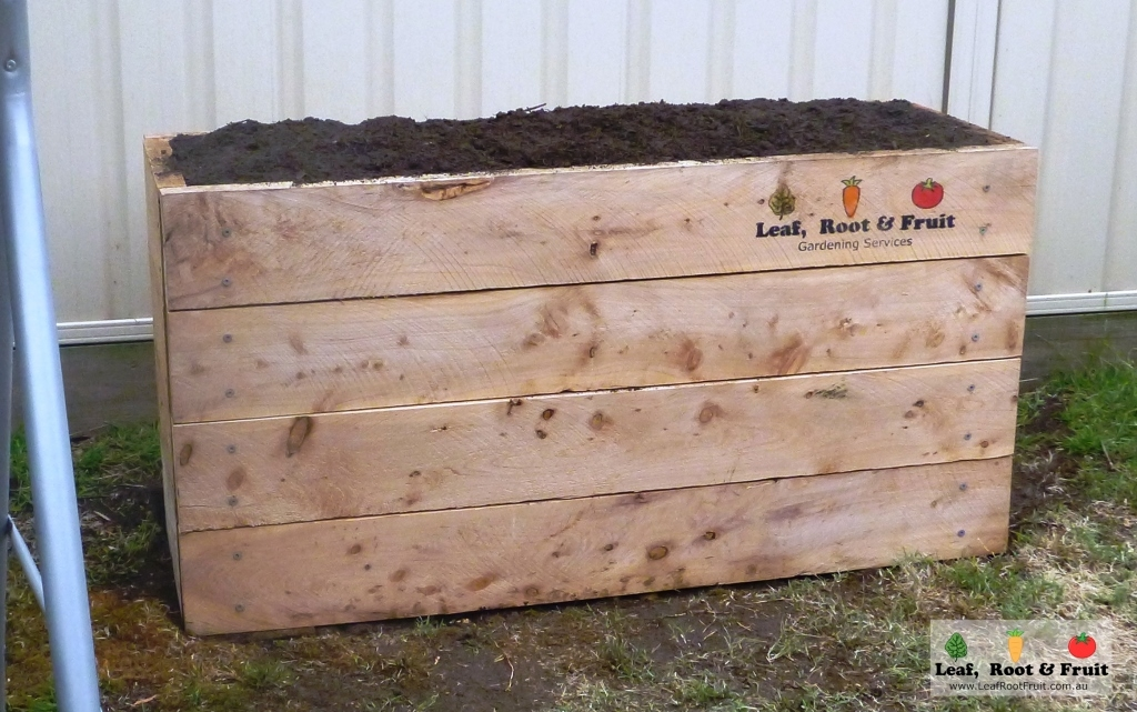 A raised cypress sleeper vegetable garden ready to plant with herbs