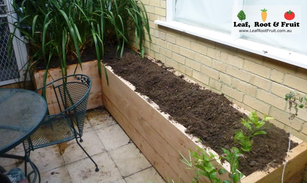 An L-shaped cypress sleeper raised garden bed
